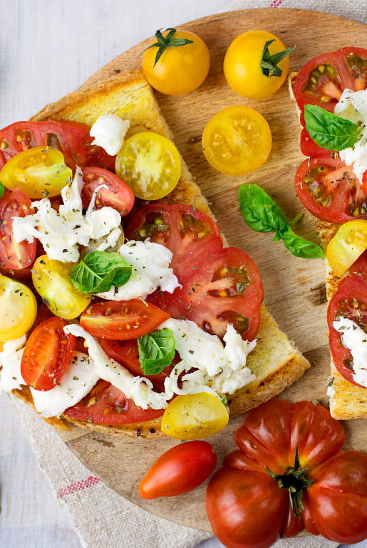 Bruschetta with three tomatoes, mozzarella and garlic oil